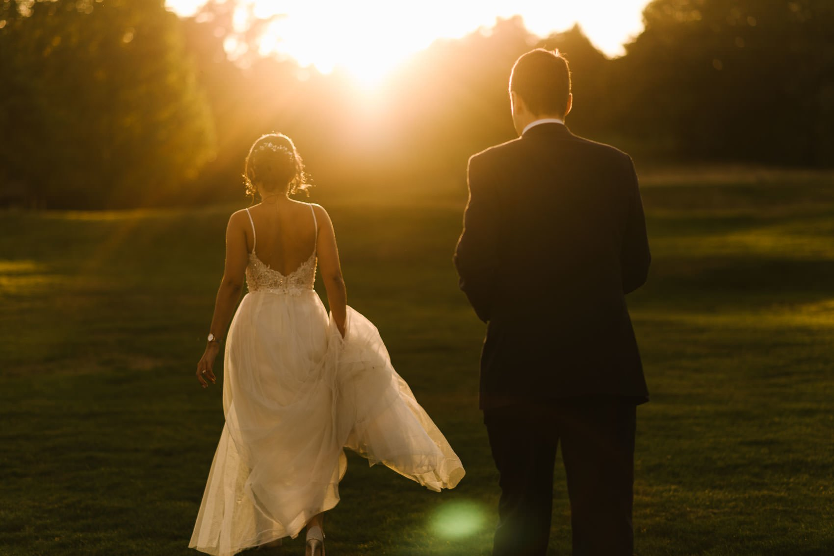Bride and groom with sunset behind them