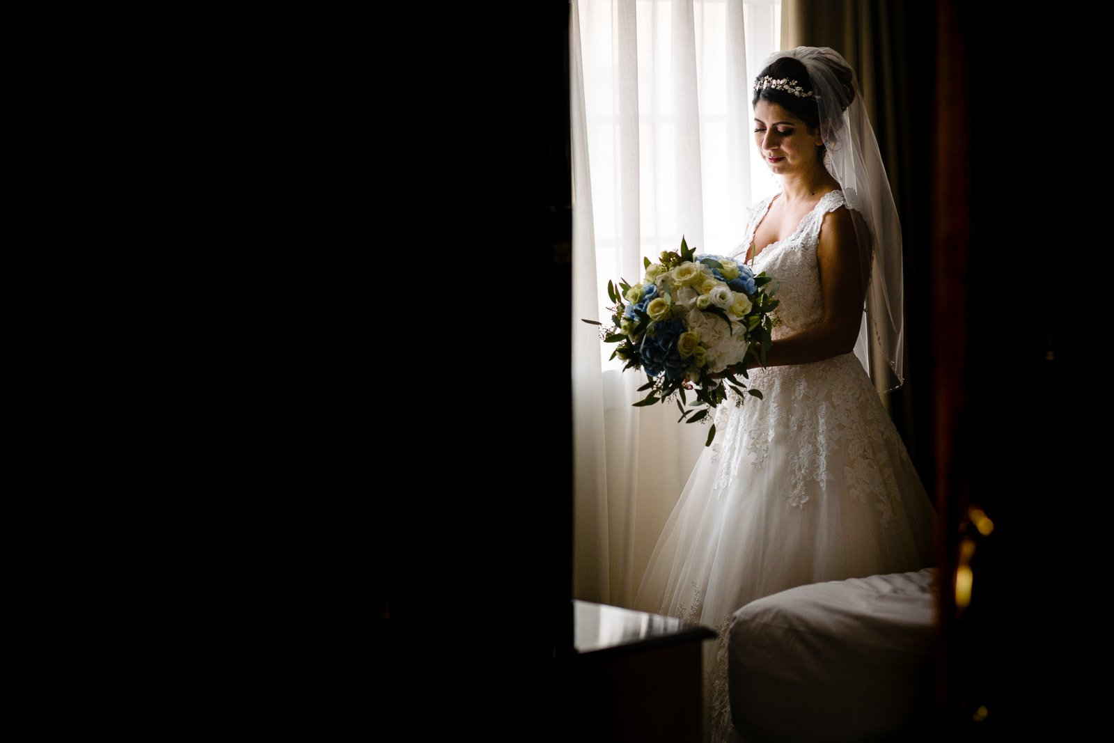 bride standing by the window looking down at her flowers