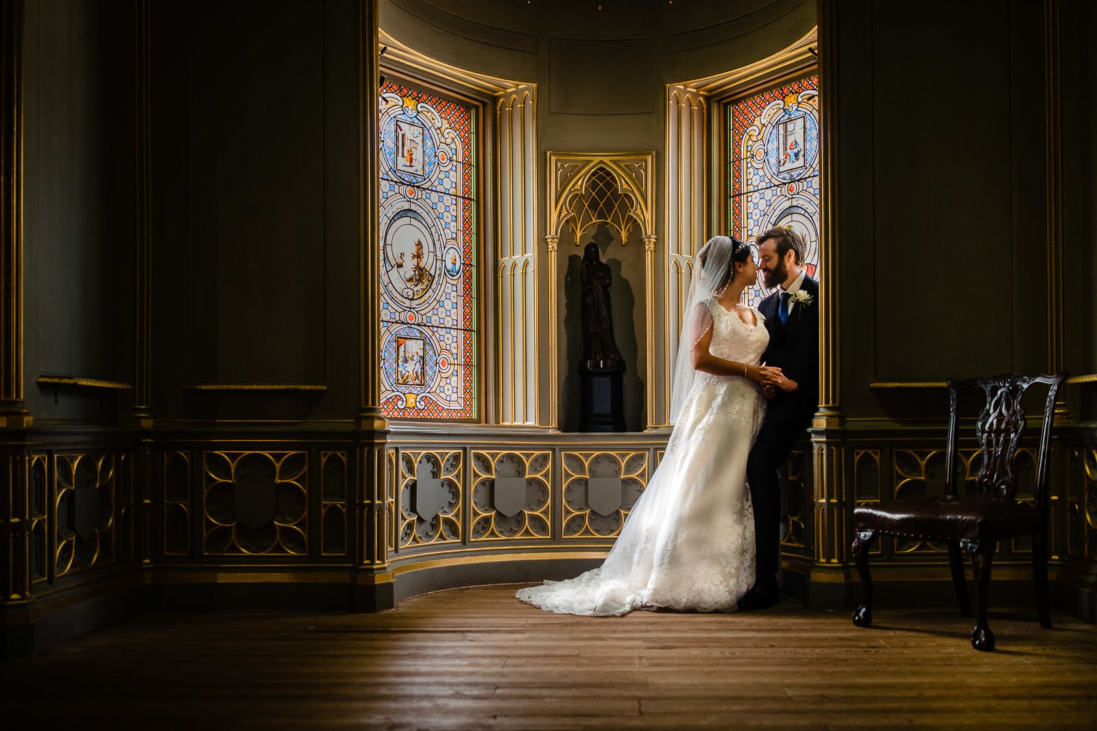 bride and groom sitting by the stained glass windows inside strawberry hill house