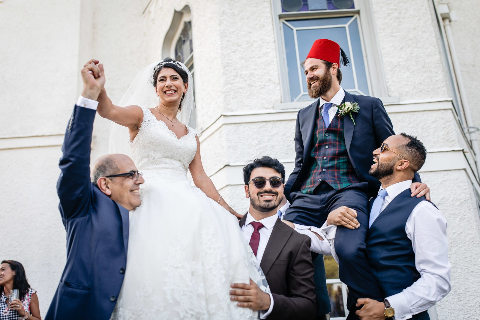bride and Groom lifted in the air during traditional dancing outside Strawberry Hill House