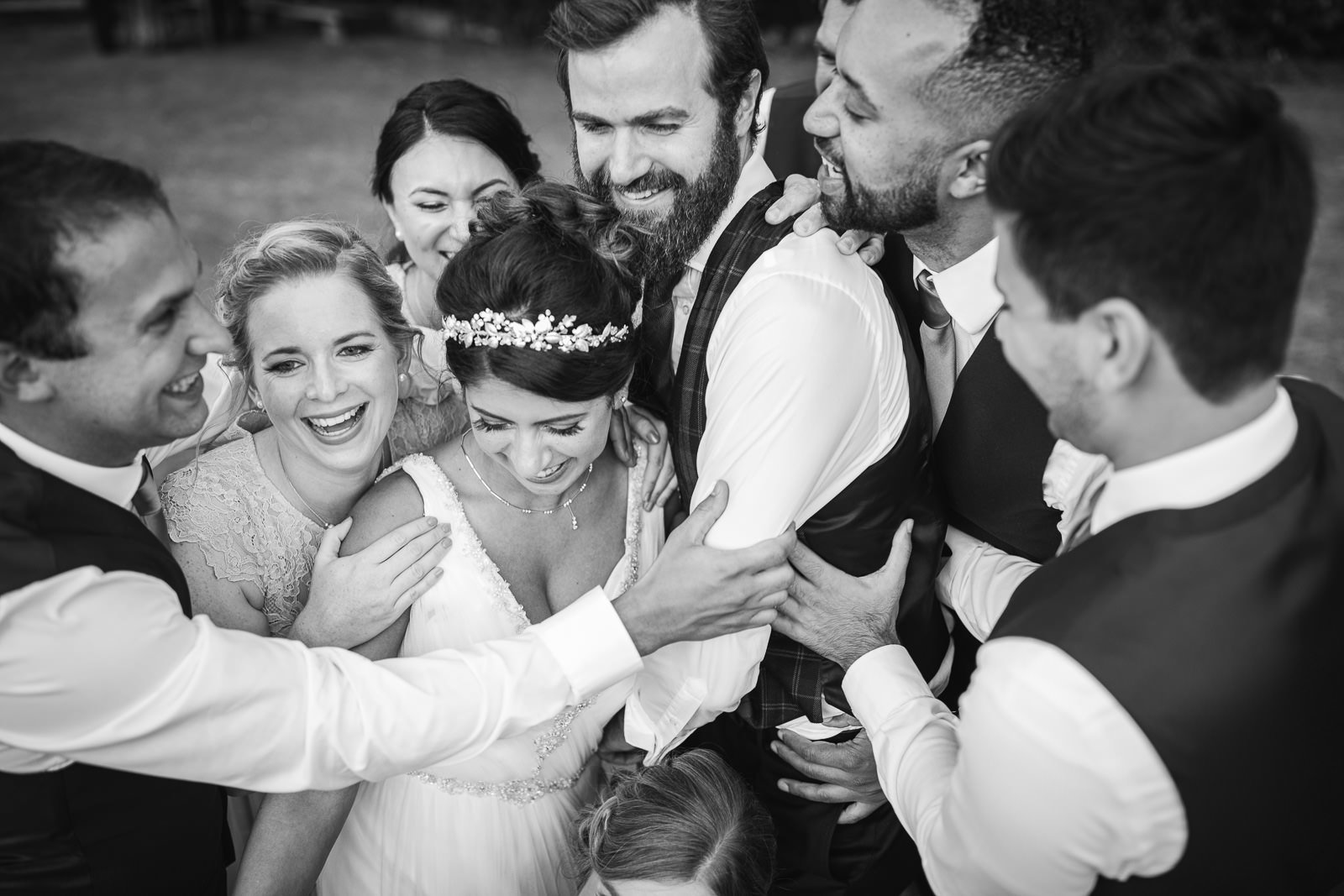 bride and groom having group hug with friends