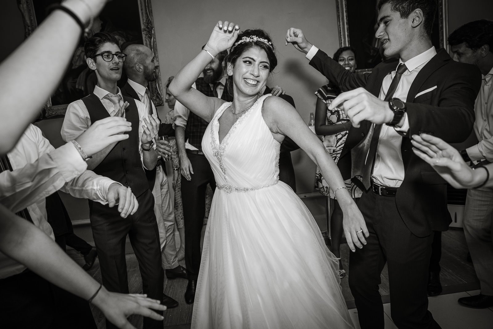 Bride smiling and dancing with lots of hands clapping